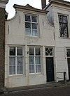 foto van Huis met ingezwenkte lijstgevel met oorspronkelijke deur en gestoken kalf