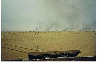 Battle of Kuwait International Airport - A United States Marine Corps tank bears witness to burning Iraqi tanks and Iraqi soldiers leaving their fighting positions at a battle that took place at Burgan Oil Field during the 1st Gulf War, February 1991.