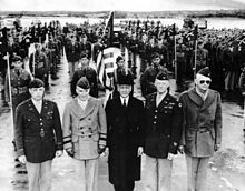 Five men in foreground, four in World War II uniform, one in the center in a suite and overcoat. Behind a color guard stands at attention, with a formation of Filipino American soldiers behind it.