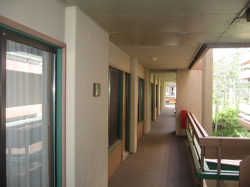 An outdoor hallway. Hotel rooms are on the left and a balcony is on the right.