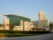A building complex with a wide glass building on the left and a tall and medium height office building on the right.
