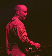 A man with a skinhead haircut sat in front of a musical keyboard. He is looking to his right, away from the camera and is shown side-on. He is wearing a jacket with embroidering on the right sleeve and is holding a drinks can in his right hand. He is bathed in red stage lights.