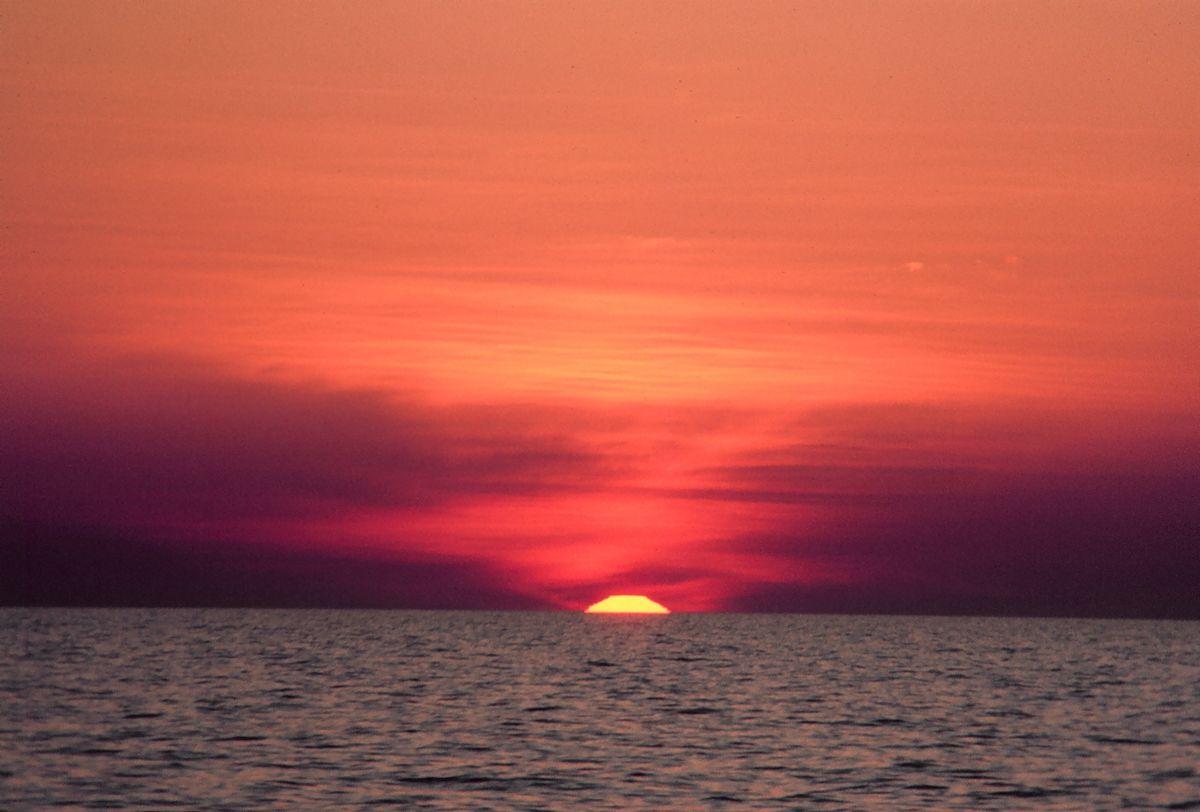 Oben roter Himmel, unten der Ozean mit kleinen Wellen wird vom Himmel erleuchtet.