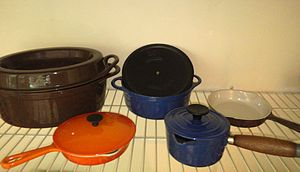 Cousances - Cousances enameled cast iron cookware. From left, the Doufeu (a slow-cooking pot roaster), small skillet, small round terrine, lipped milkpan with lid, skillet.