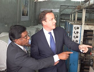 Commonwealth Heads of Government Meeting 2013 - British Prime Minister David Cameron inspecting the burnt down printing press of Uthayan in Jaffna on 15 November with E. Saravanapavan, the managing director of the newspaper and a Member of Parliament representing Jaffna.