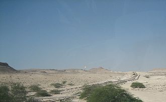 Dukhan - Pipeline system for Dukhan's oil wells. The gas flare of a petroleum refinery can be seen in the distance.