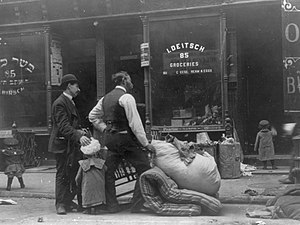 Eviction - Two men with children, being evicted, stand with their possessions on the sidewalk, circa 1910, on the Lower East Side of New York City.