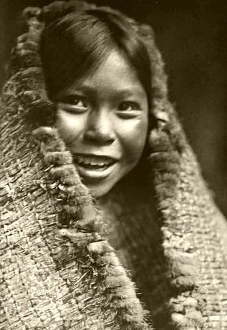 Canadian identity - Young girl from Tla-o-qui-aht First Nations in traditional tree fiber clothing - ca.1916