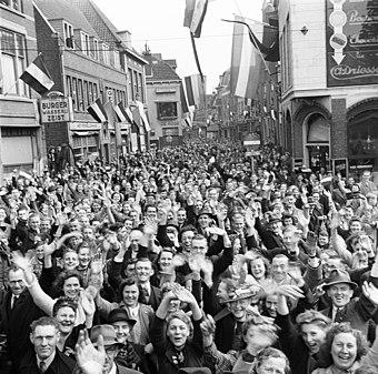 People celebrating the liberation of Utrecht at the end of World War II on 7 May 1945 Een uitzinnige menigte verwelkomt de Canadese bevrijders in Utrecht - An ecstatic crowd in Utrecht welcomes the Canadian liberators (4502667274).jpg