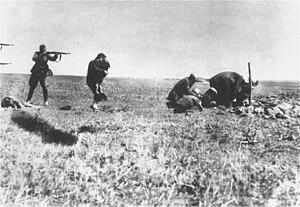 Photo noir et blanc prise à Ivangorod, en Ukraine. Dans un champ herbeux, sous un ciel clair, un soldat allemand (à gauche, au second plan), de profil, jambes écartées, tient en joue une femme qui lui tourne le dos, un enfant dans les bras. Devant le soldat, on distingue un corps de femme étendu sur le sol. Sur le bord gauche de la photo, deux canons de fusils, l'un au-dessus de l'autre, sont aussi visibles. Et, sur la droite, quatre hommes semblent creuser un trou.