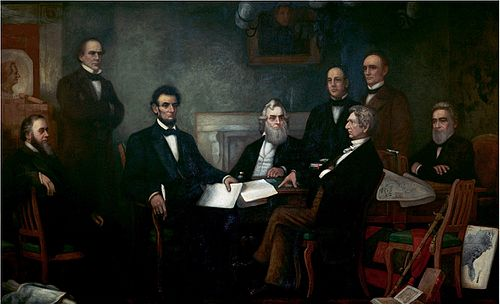 A dark-haired, bearded, middle-aged man holding documents is seated among seven other men.]]