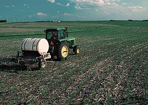Nutrient management - Nitrogen fertilizer being applied to growing corn (maize) in a contoured, no-tilled field in Iowa.