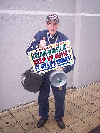 """Freddy Sez"" holding one of his signs near the bleachers entrance before a game between the Yankees and the Texas Rangers FreddySez.jpg"