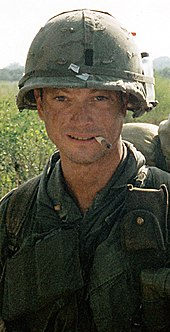 A man is at the center of the image looking at the camera. He is dressed in Vietnam War–era military attire including a vest and helmet. He has a cigarette sitting on his lips and is wearing a backpack.