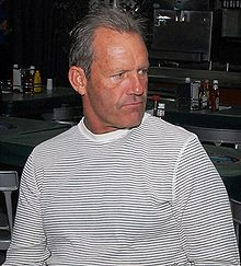 An older man with short gray hair in a black and white horizontally striped shirt looks to his left.