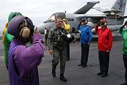 President George W. Bush on the Abraham Lincoln wearing a flight suit after landing on the aircraft carrier in a military jet.