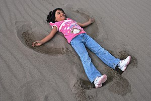 Sand art and play - Girl making a sand angel