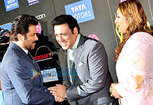 Govinda and Anil Kapoor shake hands, as Govinda's wife looks on