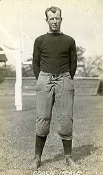 A man wearing old fashioned football gear stands with his hands crossed behind his back.