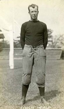 A man wearing an old-style football sweater and pants with high socks standing on a grass field with his hands behind his back