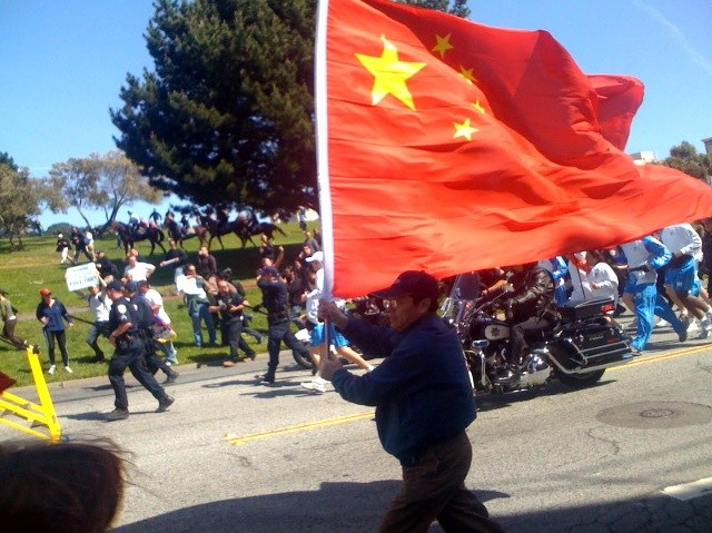Guy with a large PRC flag running along side of torch 20080409