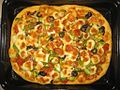 Homemade rectangular pizza in a black oven tray 05.jpg