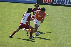Brian Ching - Brian Ching dribbles by two FC Dallas defenders in a match at Robertson Stadium on April 6, 2008.