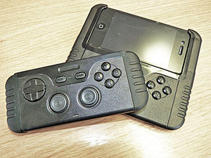Two game control devices sit atop one another. The upper is a gamepad alone, while the lower is attached to a phone.