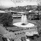 This photograph shows International Fountain in operation. Multiple parabolic arcs can be seen rising from the center of the fountain.