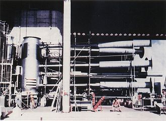 "Ivy Mike - A view of the Sausage device casing, with its instrumentation and cryogenic equipment attached. The long pipes were for measurement purposes; their function was to transmit the first radiation from the primary and secondary (""Teller light"") to instruments just as the device was detonated, before being destroyed in the explosion. Note man seated lower right for scale."