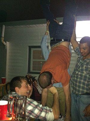 Keg stand - A keg stand. The man in the foreground is holding the tap in the stander's mouth.