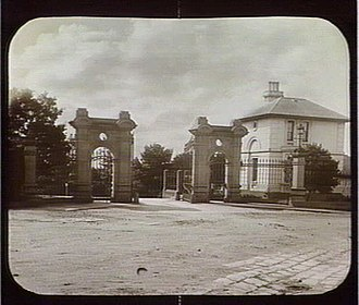 Kew Asylum - Entrance gates and gatehouse of Kew Asylum, c. 1880. The gate house was demolished and the gates moved to Victoria Park, Kew in the 1930s or 1940s to facilitate the straightening of Princess Street.