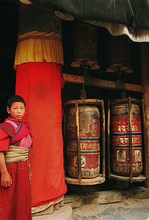 Labrang Monastery - Young monk and prayer wheels