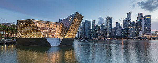 Lighted polyhedral building Louis Vuitton over the water at Marina Bay in the evening, with skyscrapers of the Central Business District in the background, Singapore