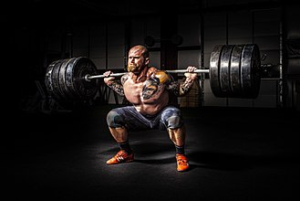 Barbell - A man lifting a barbell loaded with four weight plates on each end