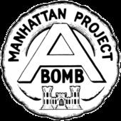 Emblème circulaire portant l'inscription «Manhattan Project» au sommet qui entoure un large «A» au centre avec le mot «bomb» écrit en dessous. L'ensemble surmonte un château qui est l'emblème du corps des ingénieurs de l'armée des États-Unis.