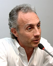 40-ish man with grey hairs, talking on a microphone.