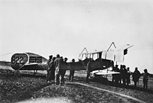 A group of men gather around a biplane. The Union Jack has been painted on to the tail of the aircraft.