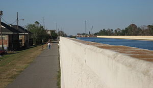 17th Street Canal - Woman walks dog along the levee beside the floodwall on the Metairie side of the canal, November 11, 2005. In the background to the right, ongoing repairs in the breach on the New Orleans side can be seen.