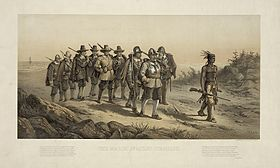 A group of nine 17th century militiamen carrying muskets and marching over a sandy path. A Native American man with feathers in his hair and carrying a musket is leading them. The soldier at the front of the group is wearing a helmet and a breastplate. In the background is a beach.