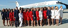 Young women in red, white and blue suits in front of a plane with a man in uniform