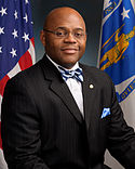 A bald African American male wearing glasses, a suit shirt and a red tie with no jacket smiles