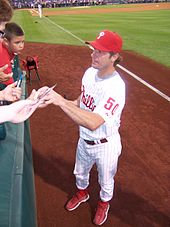 A man in a white baseball uniform with red lettering and a red hat and red shoes stands on a baseball field reaching into the stands to sign autographs for fans.