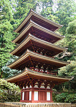 Wooden five-storied pagoda with white walls and red beams.