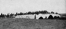 Photo shows brigade crossing the three arched stone bridge (two smaller arches on either side of a central larger arch) with the road grading up to the center and down on the ends.