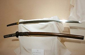 Two katana on display. The one on top has been...