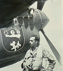 Moustachioed man in flying gear standing beneath the nose of a single-engined fighter plane, which pictures a dog and a swastika, among other items