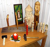 A wooden table indoors on which have been placed wooden icons.
