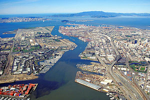 Naval Air Station Alameda - The runways and remainder of the Alameda Naval Air Station can be seen at the end of Alameda Island in this aerial view of the port of Oakland, California.