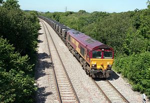 Margam Knuckle Yard - EWS Class 66 climbs Stormy Bank with a full load of Merry-Go-Round coal hoppers, after leaving Margam Knuckle Yard